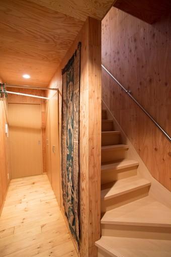 2階に上がる階段前の廊下には、来客用のコートハンガー、お気に入りのアンティークのイカット(絣)。