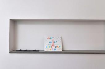 リビングのニッチには、照明用スイッチが目立たぬように仕込まれている。カードは、お子さんの生後半年を祝ったもの。