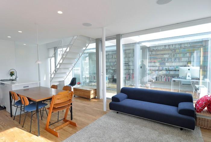 壁・天井の白とフローリングの色が基調となった空間に、ソファのネイビーとクッションの赤という配色が効果的だ。テーブル上の照明は深澤直人デザインの製品。奥のキャスター付きの収納は、ベンチ兼用でフローリングと同じ材を使って製作されたもの。