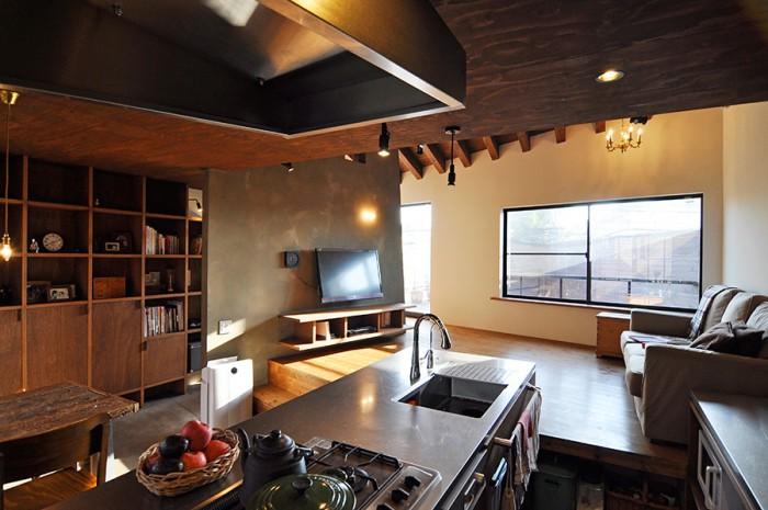 2階キッチンからリビングを見る。換気扇フードは「ごつい感じのもののほうが尾崎さん家ぽい」(建築家)と、実際の排気量からするとかなり大きめのつくり。こだわって決めたテレビの後ろの壁色はポーターズペイント社のSILT インテルノライムウォッシュ。