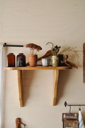 棚の上に置かれているのはアンティークの薬瓶と園芸用の鉢 をフラワーベースとして。