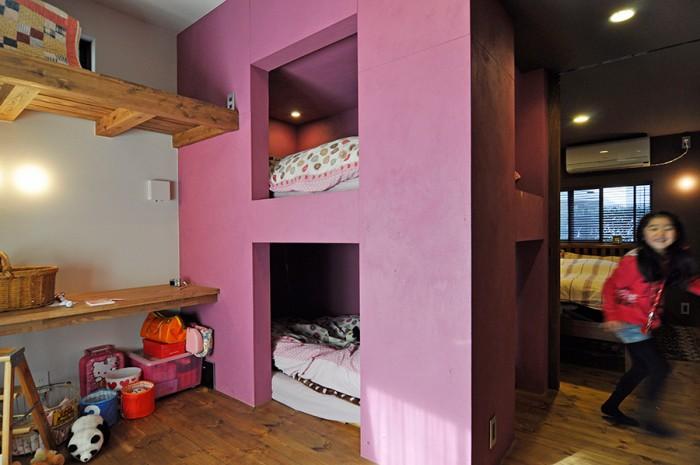 手前がお嬢さん2人のための子ども部屋。奥が主寝室。お嬢さん2人のためのベッドスペースは、ここだけ女の子らしい華やかなピンク系の色に。