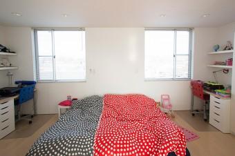 シンメトリーに設計された子供部屋。白い空間に、IKEAのシーツや雑貨が映える。