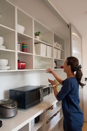 「物が取り出しやすくて便利」とキッチンに立つ妻・佳子さん。引戸はクローゼット用のドアを使用した。
