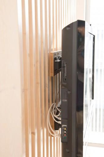 壁掛けにしたテレビ。ルーバーの間に配線が収まるというグッドアイデア。