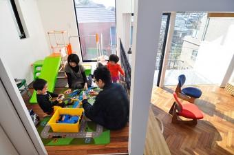 リビングより半階高い子ども部屋の一家4 人。リビングから、子 ども部屋で遊ぶ2 人のお子さんの姿がよく見える。