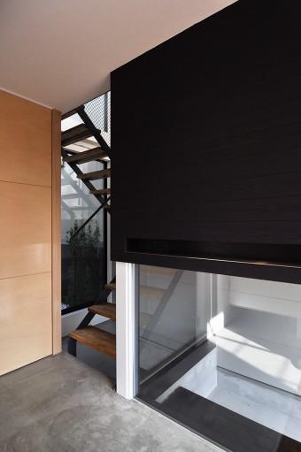 1 階玄関ホールの床はコンクリート仕上げ。これに合わせて 壁を黒の杉板張りに。