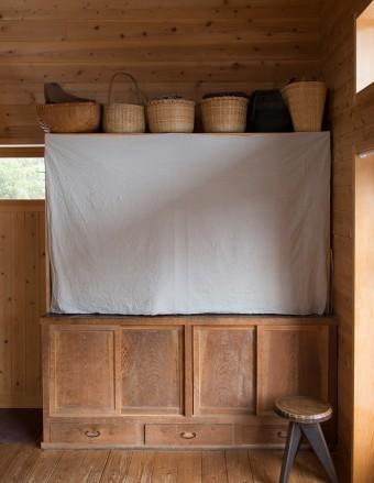 古道具屋で見つけた箪笥の上に、自作の棚を乗せている。ここに家族4人分の服が収められている。