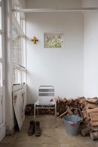 アトリエの前室の土間のスペース。土の上に直接敷いたコンクリートブロックの上に、アトリエのストーブ用の薪が積んである。