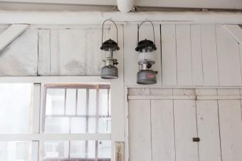 コールマンのランタンや、スチールがいい感じに錆びた寒暖計…。ひとつひとつのモノ選びに、仲田さんのセンスとこだわりを感じる。窓の向こうに見えるのが風呂小屋。