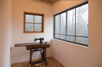 かおりさんの嫁入り道具の古いミシン。「いい窓が見つかったので、いつか奥の木枠の窓と入れ替えたいと思っているんです」と智さん。