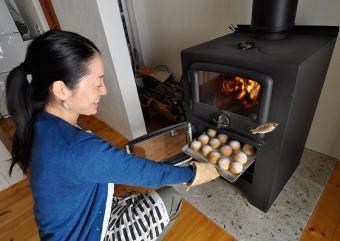 オーブンで焼いたパンを取り出す奥さん。