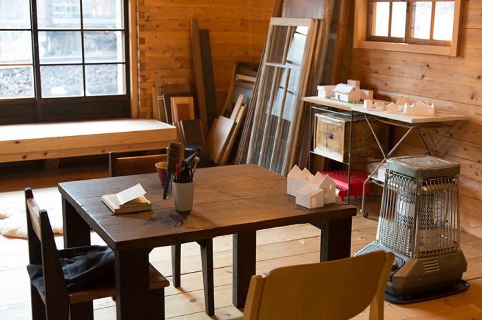 益子の木工作家・高山英樹さんの作ったテーブルで、クライアントとの打ち合わせも。奥に立てかけてあるのは、古い建具のストック。