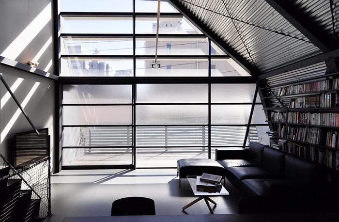 3階LDK空間。キッチンからバルコニー側を見ると、本棚部分以外はほぼ無彩色の世界。ソファはこの家のために建築家がデザインしたオリジナル。切り詰められたデザインが空間にとてもフィットしている。