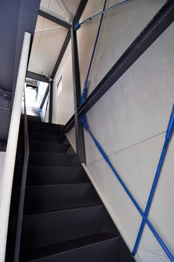 1階から3階まで続く直進階段。こちら側の壁は、青いブレースがずっと続く。