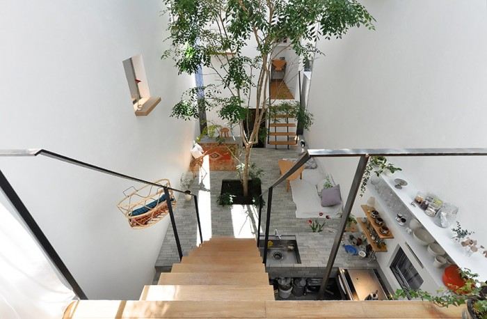 """真矢さんの仕事場から""""広場""""を見下ろす。右下にキッチン。向かいのやや細長い形状をした箱には、下から、バスなどの水回り、書斎、寝室が収められている。仕事場も含め、どの空間にも扉がないため、とても奥行き感が感じられる。"""