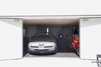 車はアルファロメオ スパイダー。右にイタリアのスポーツバイク、ドゥカティ。シャッターではないため、この両開きの戸を閉 めると、外からはガレージのようには見えない。