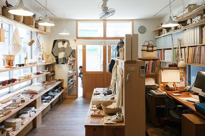 事務所とお店は本棚で仕切られている。白いペンダントライトは工場などでよく使われる笠松電機製作所のもの。