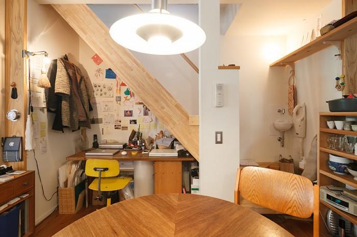 階段下は眞紀さんのワークスーペース。黄色いデンマーク製の椅子は、古道具屋で求めたもの。ダイニングの照明はヨルゲン ガメルゴーのデザイン。