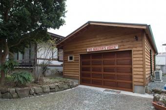 """キットを輸入して作った大型のガレージには、入川さんの遊び道具が満載。入り口には、ビクターの工場から譲り受けた""""HIS MASTER'S VOICE""""の看板がかかる。"""