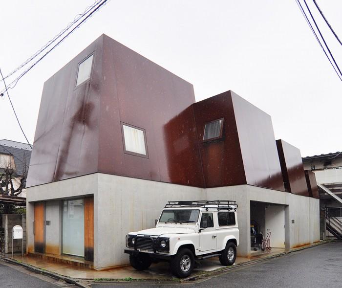 2・3階部分のコールテン鋼が赤味を帯びているのは錆のため。雨のためいつもより濃いめの色合いに。山が連なるような外観に、滝川さんの愛車、ランドローバ― ディフェンダーがしっくりと合う。2世帯住宅で、1階に親世帯、2・3階に子世帯が住む。
