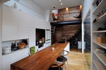 キッチンとダイニングにまたがる、長さ約3.8mのテーブルは存在感抜群。椅子はハンス・J・ウェグナーのアームチェア。