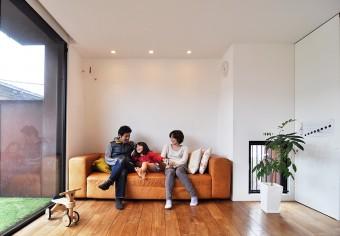 ベランダに面したリビング部分のソファでくつろぐ。夫妻ともに、グラフィックデザイン関係の仕事をされている。