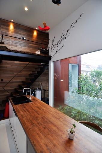 """テーブルと木壁、シマトネリコと""""自然""""を感じる要素に囲まれたDK。さらに白壁には桜の枝を模した装飾も。"""