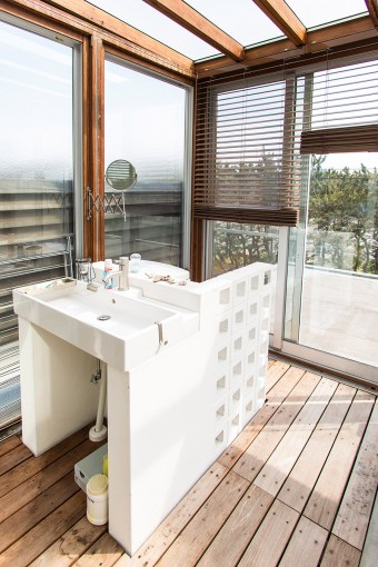 たっぷりと陽が差す洗面台の裏は、絶景のトイレ。防砂林の向こうに海が広がっている。