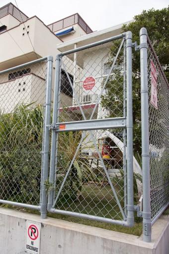 米軍住宅にありそうな武骨な鉄柵。サーフボードやカヤックの出し入れのために、道路に面した場所に扉を作った。