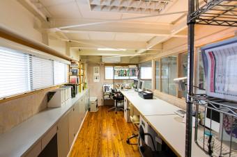 中2階にある事務所で、日中はふたり揃って仕事。窓からは、ガレージの愛車が見下ろせる。