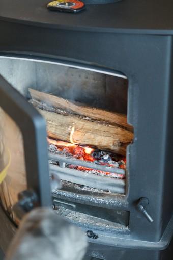 ガラス扉を空けて、薪をくべる。火の世話をするのも、薪ストーブの楽しみのひとつ。