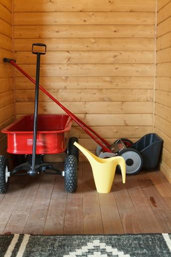 板張りの玄関には、芝刈り機(右)と薪運び用の手押し車がスタンバイ。