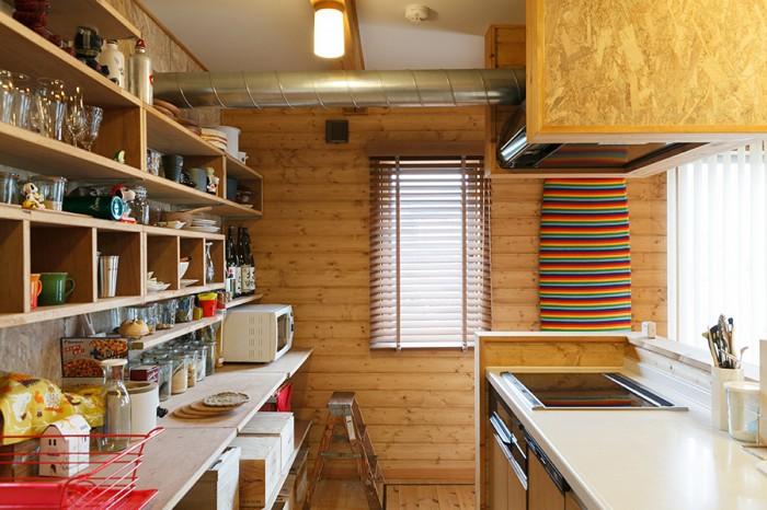 オープンなつくりのキッチン。カウンター下もワインの木箱などを利用して収納している。奥の壁に立てかけたサーフボードは奥さんのもの。