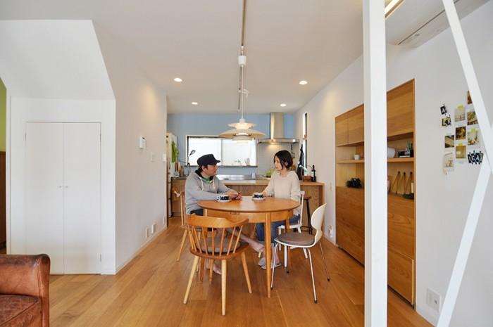 リビングからDKを見る。パーティなどで大人数になったときは、テーブルの天板を左右にスライドさせて大きくして対応。左の壁の中身は階段室+収納。