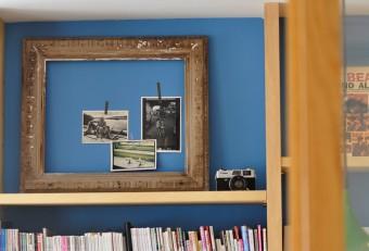 土間の本棚奥の壁に貼られた写真が納まるようにフレームが置かれている。左はキャパ撮影のヘミングウェイ親子の写真。