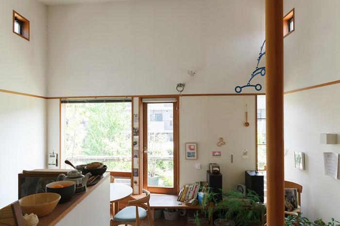 階段からダイニングキッチンを見る。南側に面して効果的に配された窓からの光が部屋を満たす。窓の外にはバルコニーがあり、たくさんの鉢植えが並べられている。また天井近くのハイサイドライトは開閉可能で、夏は開けて熱気を外に逃がす働きをする。