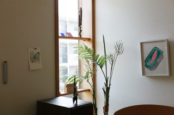 壁は石膏ボードの上にケナフ紙張り。友人たちの作品を飾っている。ポストカードは得地直美さん、版画は小井田由貴さんの作品。