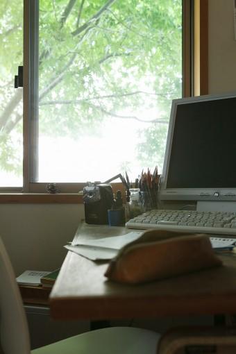 仕事場の窓からは、アプローチに植えた樹木の緑が見える。エアコンは設置していないが、夏も木陰のおかげで涼しく過ごせる。