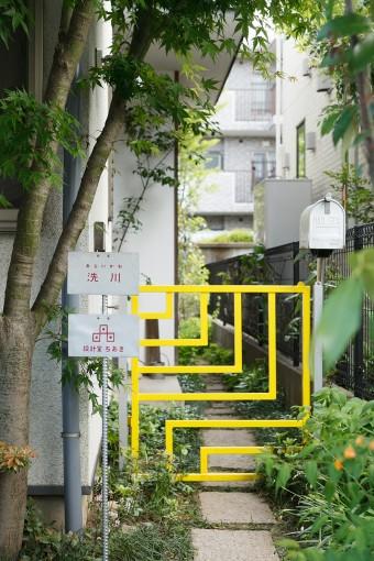 黄色の門扉は本間純さんの作。外観のアクセントになっている。