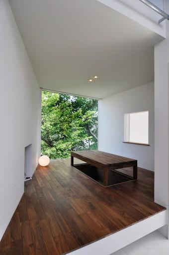 間に玄関を挟んでキッチンの向かいにある〇〇。裏にある緑が開口でうまくフレーミングされている。