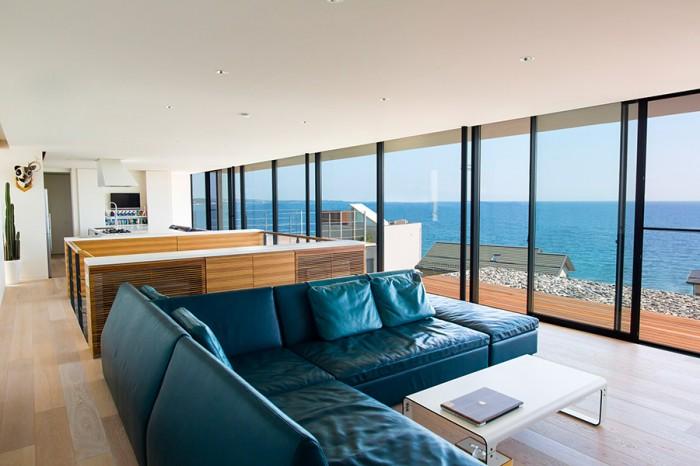 内田宅の2階は、水平線を堪能できる大空間がメインテーマ。構造計算の専門家にお願いして、南側の開口部を大きく確保。手前のグリーンのレザーソファは、家具デザイナーの藤城成貴さんの作品。