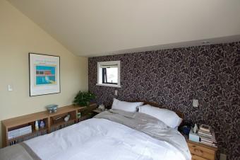 ベッドルームにもウイリアム・モリスの壁紙を採用。柄が印象的な分、ベッドリネンはシンプルに。