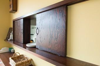 キッチンとダイニングをつなぐ小窓。その手前には、カトラリーやクロスを入れるキャビネットを置き、サーブしやすさに配慮。