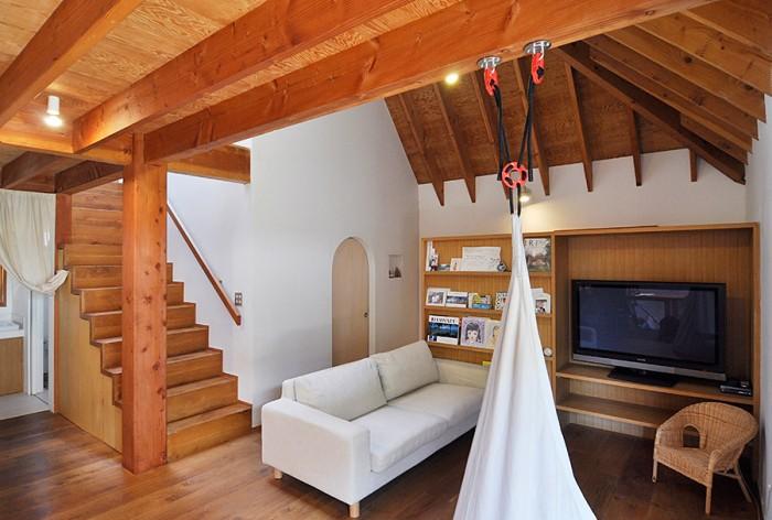 テレビの置かれている壁面の裏が玄関。リビングには布製のブランコが吊るされている。