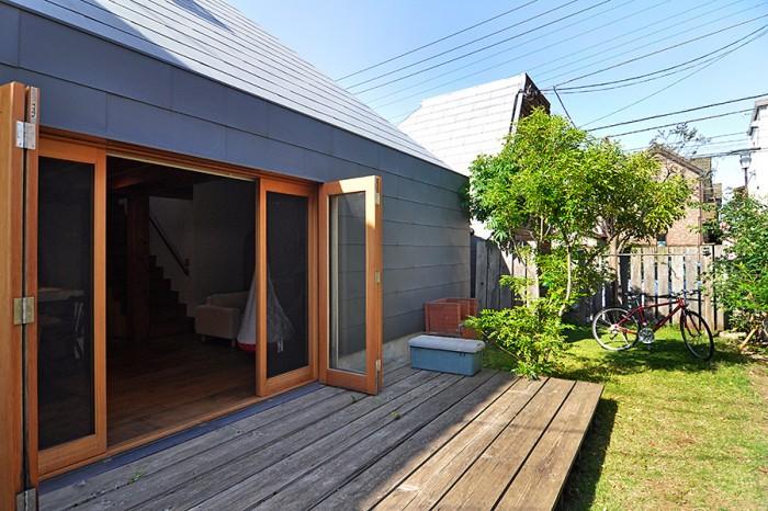 屋根・外壁はガルバリウム鋼板。壁際にはバーベキュー用の煉瓦が積まれている。奥に見えるのはパン屋さんの屋根。