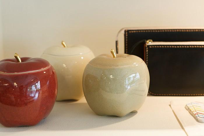"""鹿児島県の沈壽官窯と共同でスタートをしたCHIN JUKAN POTTERYの シュガーポット。リアルなフォルムと今までの薩摩焼にはない絶妙な色の釉薬が特徴。右に見えるのも""""さつまもの""""のRHYTHMの黒財布。"""