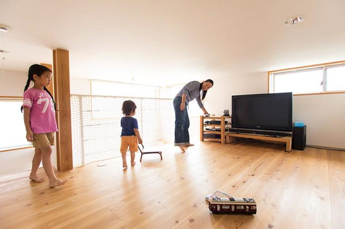 吹き抜けに面したロフトで遊ぶ子どもたちと美穂さん。条例でロフトに付けられる窓の大きさが制限されているため、大きな吹き抜けをつくり窓を設けて光を導いた。ロフトの天井高は1メートル40センチなので、子どもはそのまま走りまわれる。