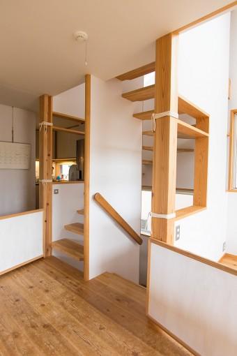 階段の壁に穴を空けて、光と風の通り道に。奥のキッチンの気配も、階段の穴をとおして感じられる。階段の柱に取り付けた板は、犬たちの登り下りを防ぐために、美穂さんがDIYでつくったもの。