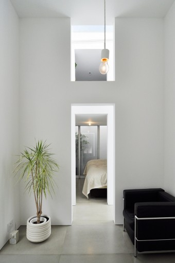 リビングから寝室を見る。右はル・コルビュジエのソファ〈LC2〉。リビングの天井高は3.9m。